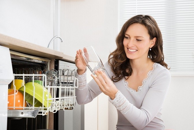 lady looking at dishes in dishwasher